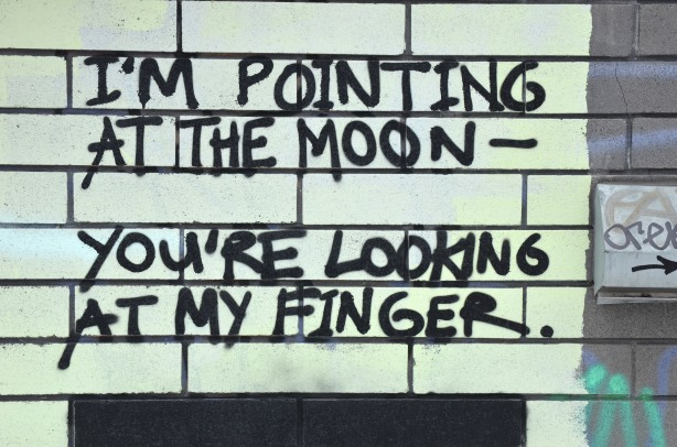 graffiti that says I'm pointing at the moon - You're looking at my finger