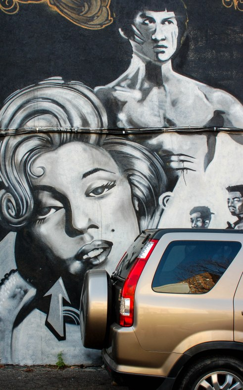 Street art painting in grey tones, a topless Bruce Lee  is standing behind the head and shoulders of Marilyn Munro.
