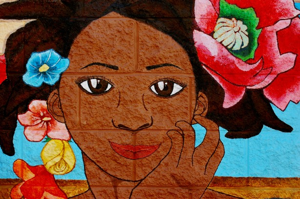 street art painting of a brown woman's face, black hair and flowers in her hair.  Brown eyes, and smiling red lips
