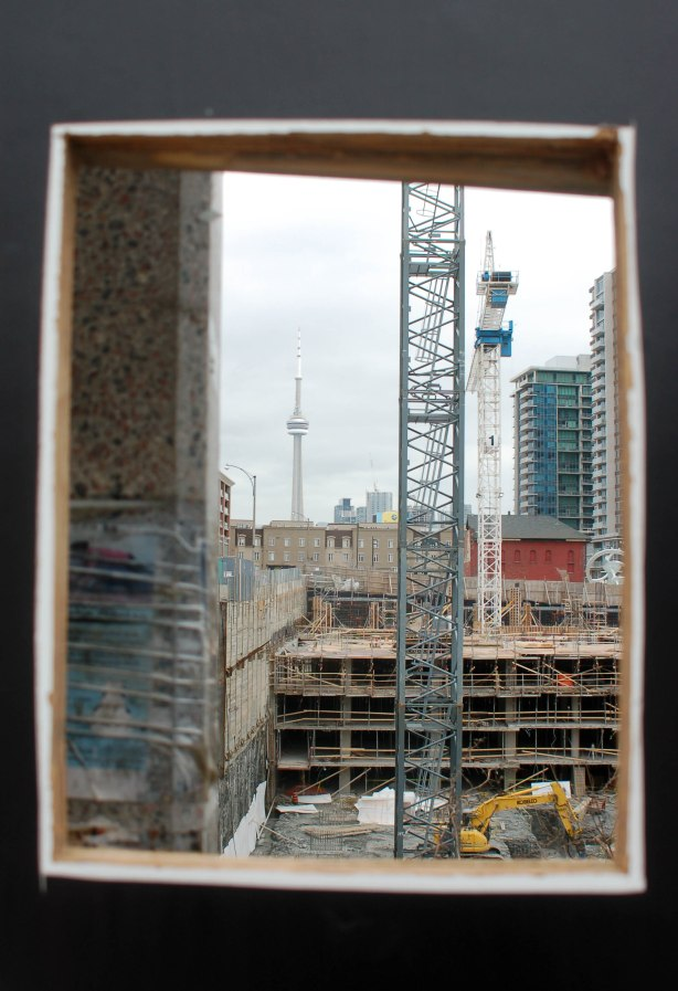 This picture was taken through a cut out hole in a black fence around a large construction site for a new condo.  The construction is in the foreground, the CN tower is in the background.