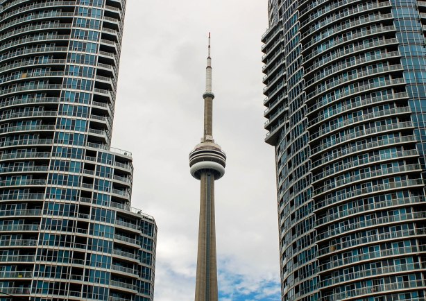 The CN tower is between two large condo towers