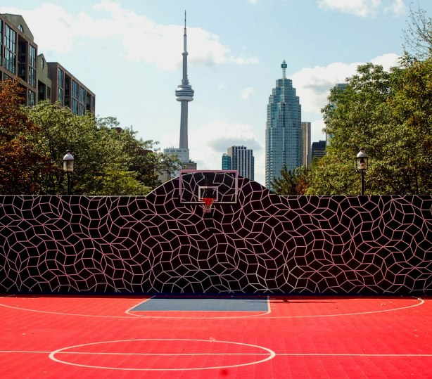 red surfaced basketball court in the foreground, then a black and purple fence, and then downtown Toronto in the background.