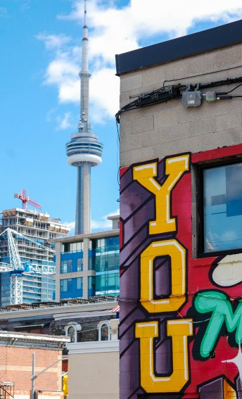 A building with the word you written in large yellow letters is in the foreground.  The CN tower is in the background.