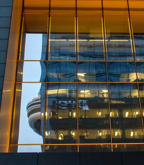 Early evening, the CN tower is refleceted in an office building.  The lights are on and you can see people working in the building.