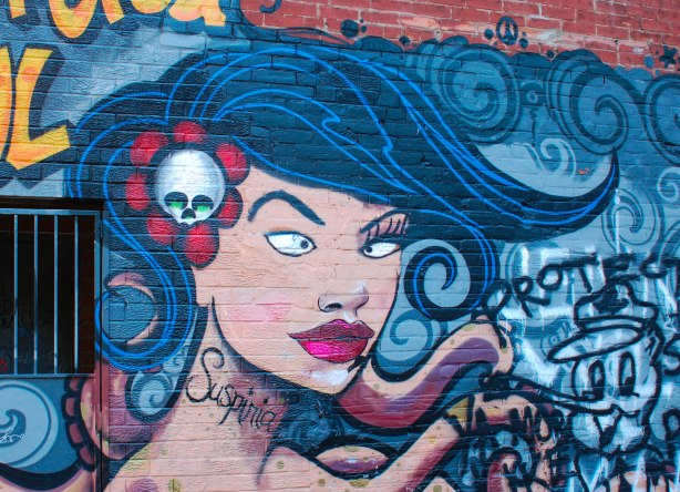 Suspiria street art painting of a woman's head on an octopus body.  Blue flowing hair, a skull in her hair.