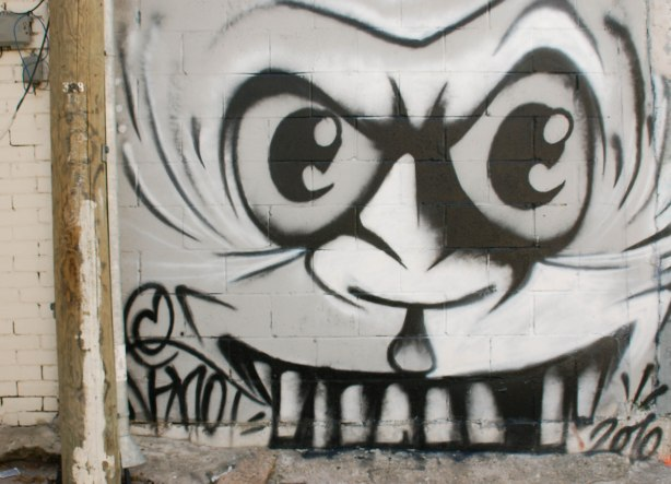 street art in black, white and grey of a large angry face with big teeth