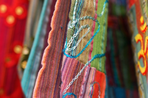 close up photograph of colourful bags for sale.  One of them is a green, pink and purple striped fabric with embroidery on it.