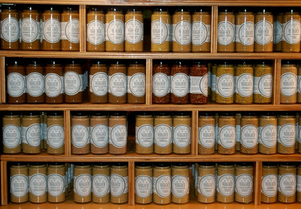 many varieties of Koslicks mustard in a display.  Jars of the different kinds are grouped together.