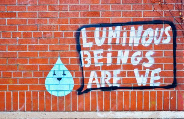 graffiti that  says luminous beings are we