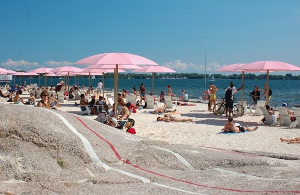 Lots of people under pink umbrellas at Sugar Beach.