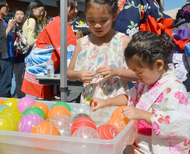 two girls dressed in kimonos trying to grab a small inflated balloon that is floating in water.