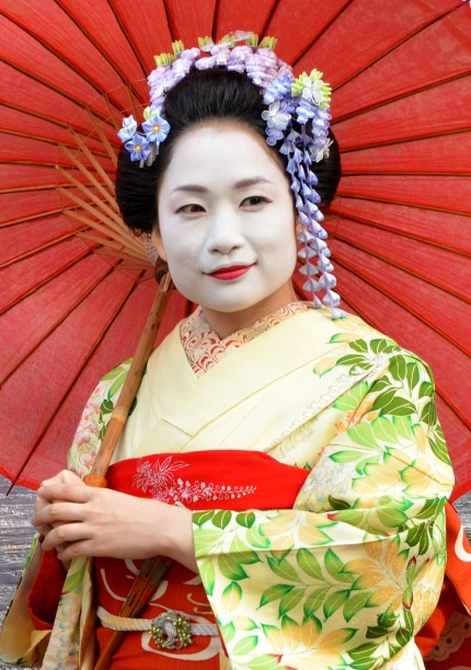 geisha with makeup and red parasol.   She has flowers in her hair and she is wearing a yellow and green kimono.