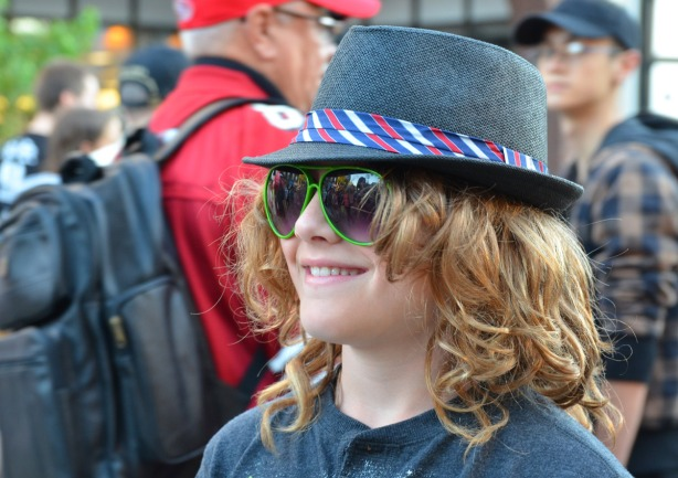 big sunglasses, a fedora, and a big smile!