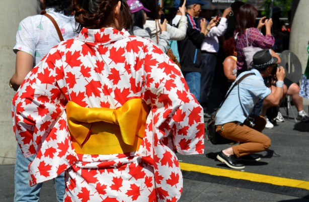 A woman wearing a kimono made of fabric that is covered with red maple leaves.