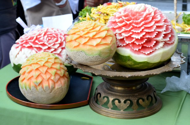 canteloupes and watermelon that have been carved to look like flowers with many petals