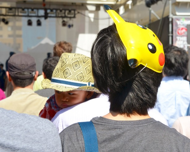 A man wearing a Pokemon mask on the side of his head.  Also in the photo is a small boy wearing a fedora but falling asleep on his father's shoulder