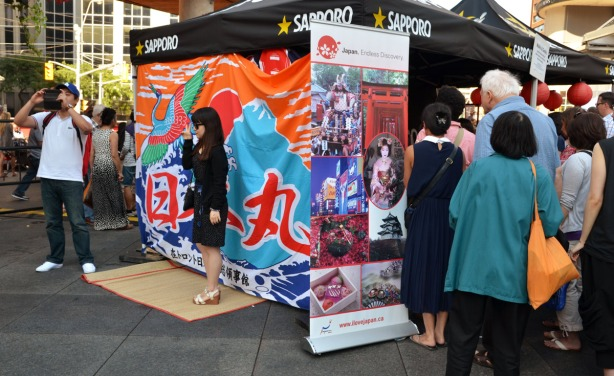 people standing around a booth sponsored by the beer company Sapporo.  One woman is having her photo taken.  A group of people are waiting in line to go into the booth