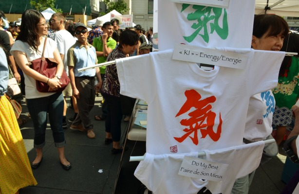 "Display of T-shirts for sale.  They have Japanese writing on  them.  One is the character for energy and the other is the character for ""be yourself'"