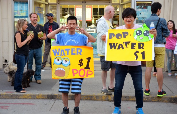 two guys wearing bright yellow signs advertising the fact htat they are selling pop and water