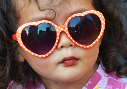 a little girl wearing big orange and white heart shaped sunglasses