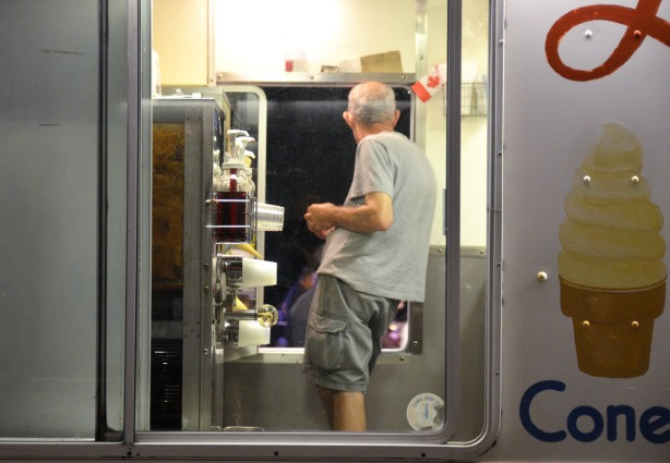 man inside an ice cream truck, his back is turned to the camera and he is looking out the window