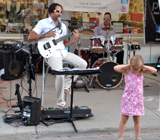 girl covering her ears with her hands while standing in from of a guitar player.
