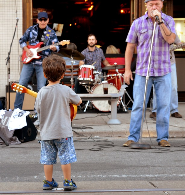 little kid with toy guitar watching a band play