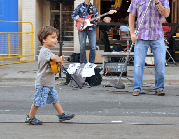 boy with toy guitar walking in front of a live band
