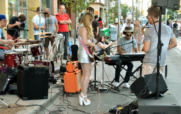 girl with very short silver skirt and very high white shoes is playing a guitar in a band.  Many people are watching