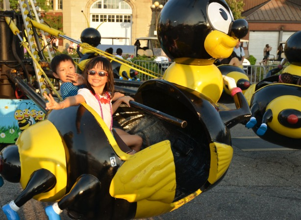 two kids on a large bumble bee, one of the rides in Kid Land at the CNE