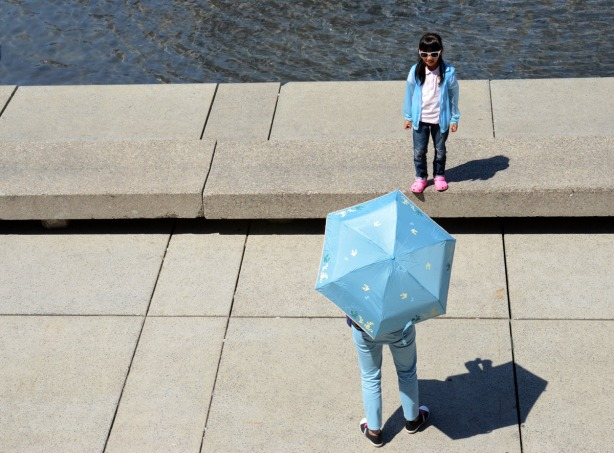 A girls wearing a light blue jacket is standing beside the pool at Nathan Phillips Square while her mother takes her picture. The mother is wearing light blue pants and is holding a light blue umbrella.