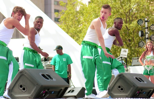 4 men dancing on a stage.  they are wearing green pants and white sleeveless T-shirts.