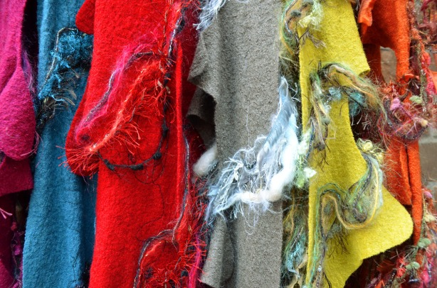 pieces of felt in blue, red, grey and yellow hanging in a vendor's stall at an arts and crafts fair