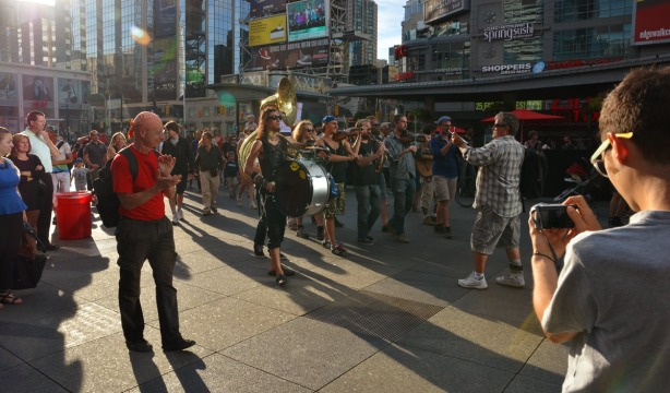 man with an iphone standing in front of the Lemon Bucket Orkestra as they walk through Dundas Square.