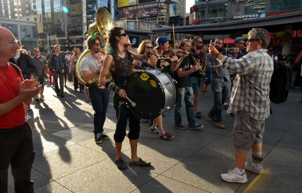 man taking pictures of a group of musicians, a drummer, a clarinet player, some violins and a flugelhorn