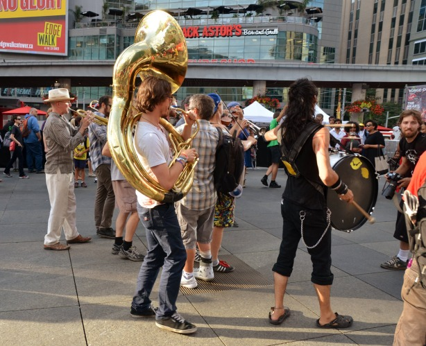 man is standing in the middle of a group of musicians, the Lemon Bucket Orkestra, as it walks through Dundas Square.