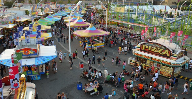 birds eye view of the midway.  multicoloured roofs over midway game stalls, lots of people walking around