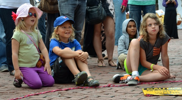 four children sitting on the ground and watching a magic show.  Three are smiling, one is looking skeptical.