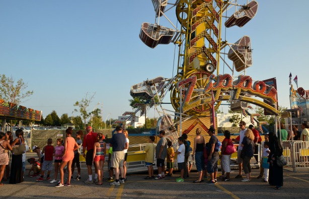 many people in a line up waiting to get on the Zipper ride