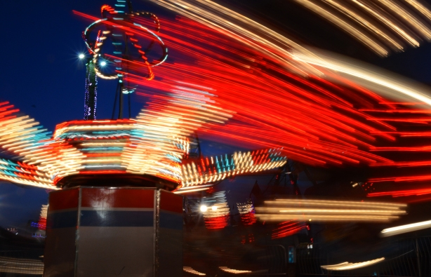 blurred lights in red, white and blue, as one of the rides spins around