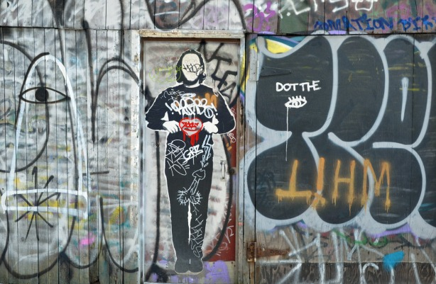 Black and white graffiti on a wall and door.  There is life sized picture of a man on the door.  He is holding a red heart in his hands.