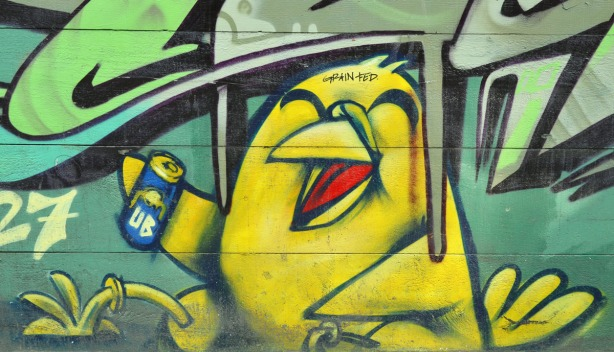 Uber's yellow bird is laughing and drinking something from a can.  Somone has added the words grain fed to his forehead.