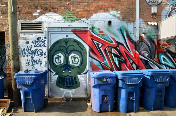 back of a building on Queen St. that has a large red and blue tag on it.  There is a large green skull-like picture on the door.  Four blue recylcing bins are by the door.