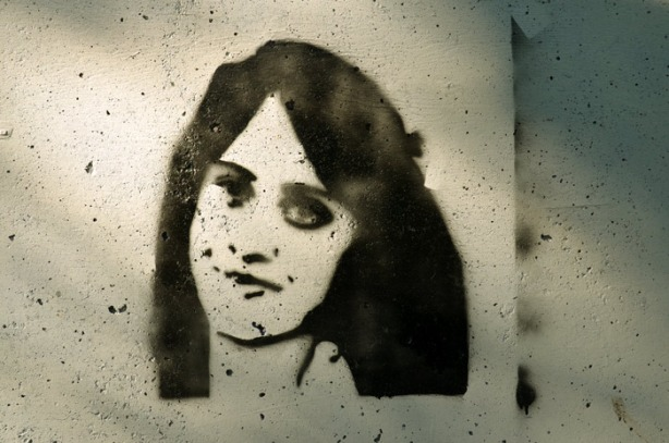 a stencil graffiti in black and white of a woman's face.