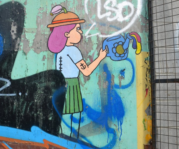 graffiti of a girl with a watering can.  The girl has a tottoo of an anchor on her upper arm.  She has purple hair and she is wearing a hat with a feather in it. She is also wearing a green skirt.
