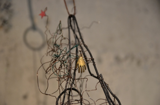 part of a wire sculpture showing a little gold trinket in the shape of a hand