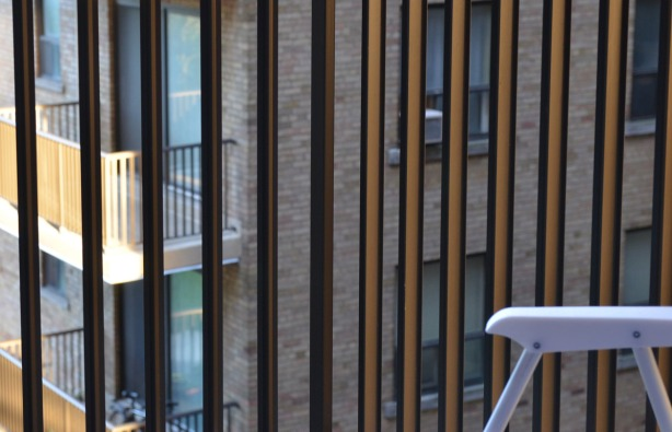 looking through the railing of a balcony towards other apartments and their balconies