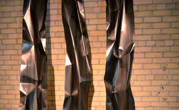 A sculpture that is composed of three tall vertical pieces of shiny metal.  A yellowish brick wall is in the background.