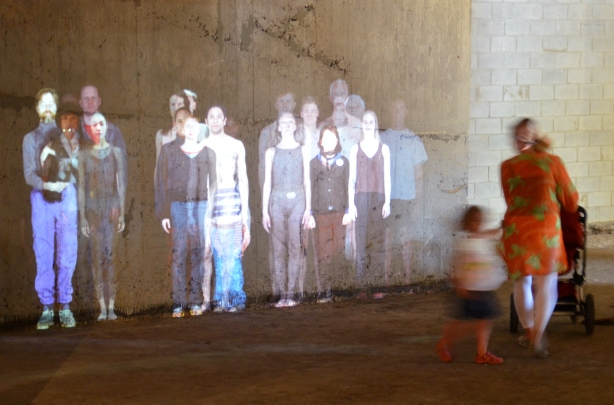 life sized projection of a group of people, male and female, young and old,