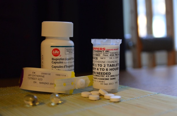 pills and a hospital ID tag sitting on a table.